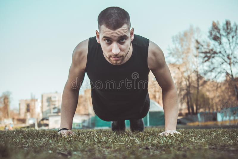 Young man in sportswear does exercises on the grass at the stadium. training on the ground. press-up. push-ups.  stock images