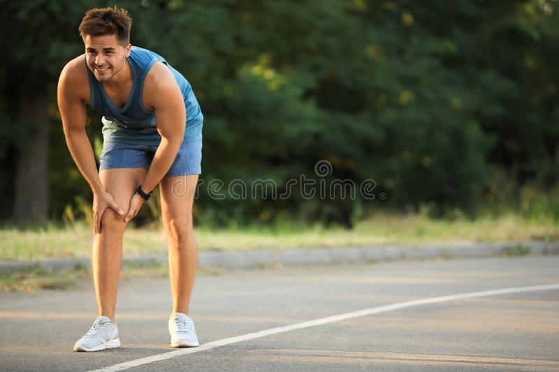 Young man in sportswear having knee problems stock photo