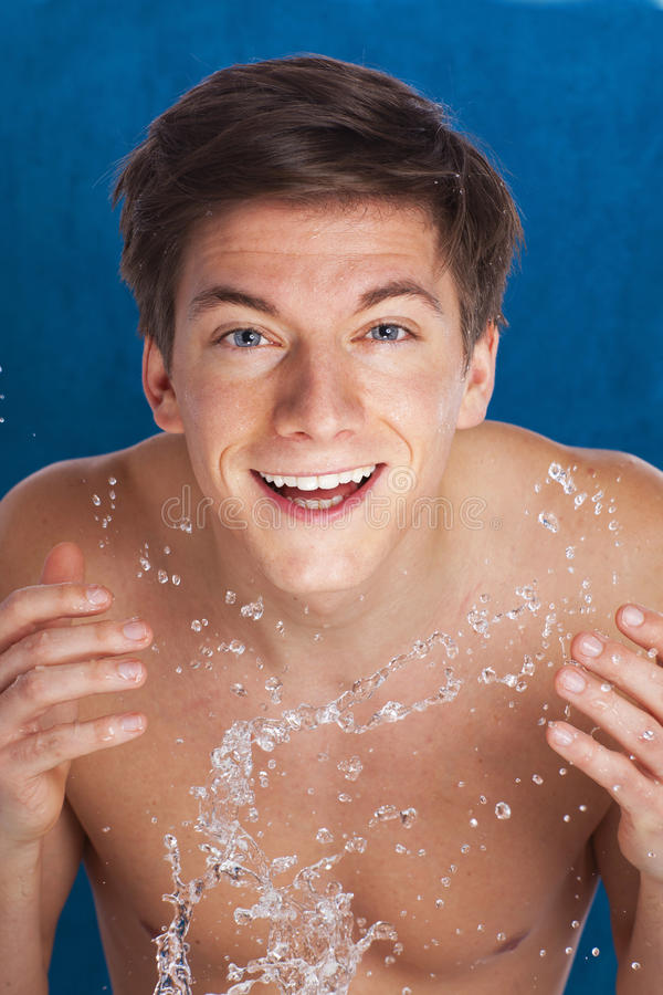 Young man spraying water at his face stock images