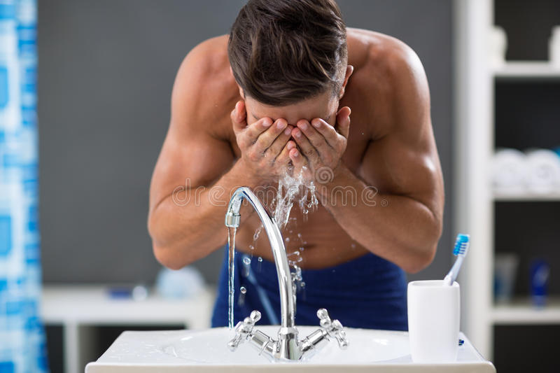 Young man spraying water on his face after shaving. Splashing water on his face stock images