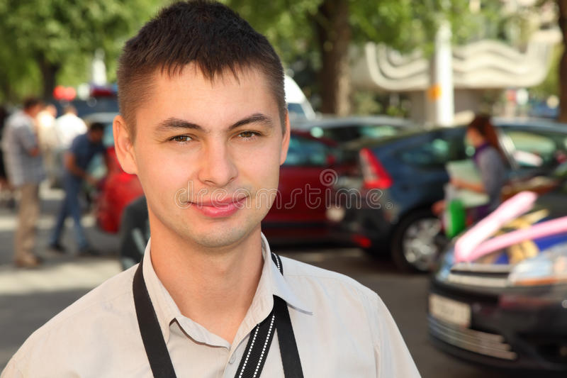 Young man stand near cars. Young man wearing white shirt with belts of camera stand near cars royalty free stock photos