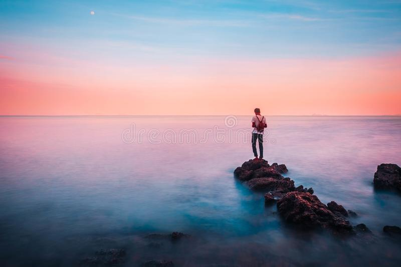 Young man stand on a rock in the foreground of him have the sea and sky brightly colored look like a dream in heaven. stock photos