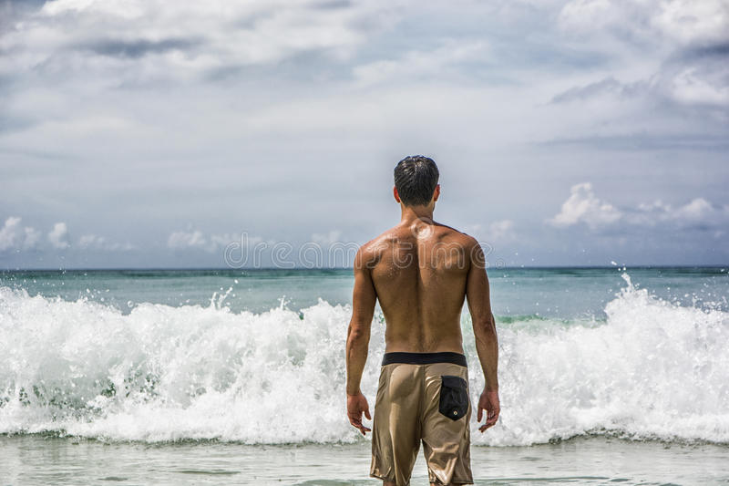 Young man standing on beach by the ocean royalty free stock images