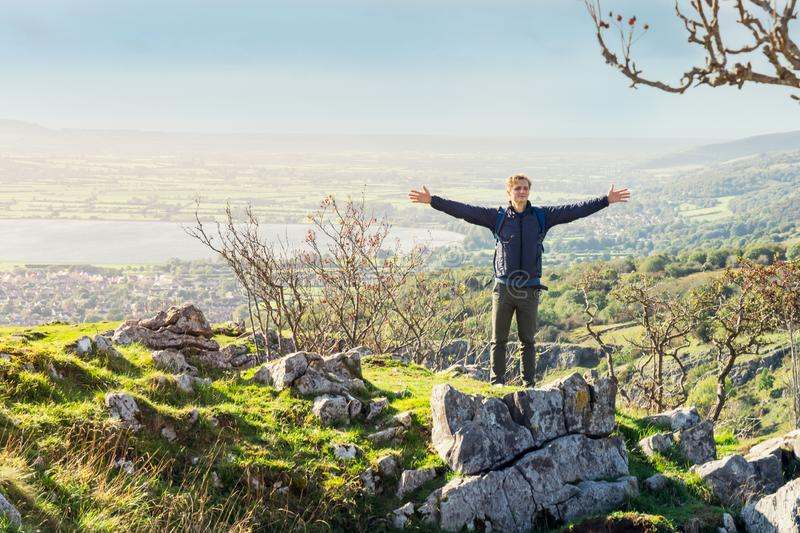 Young man standing on big stone on mountain with raised hands with forest, lake, countryside landscape on background. Travel. Lifestyle wanderlust adventure royalty free stock photo