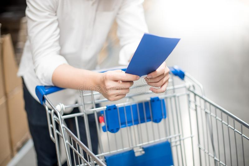 Young man checking the shopping list in warehouse. Young man standing with cart checking the shopping list in warehouse wholesale, shopping warehousing concept stock photography