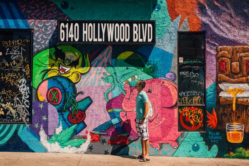 Young man standing by the colorful graffiti wall in Los Angeles stock photos