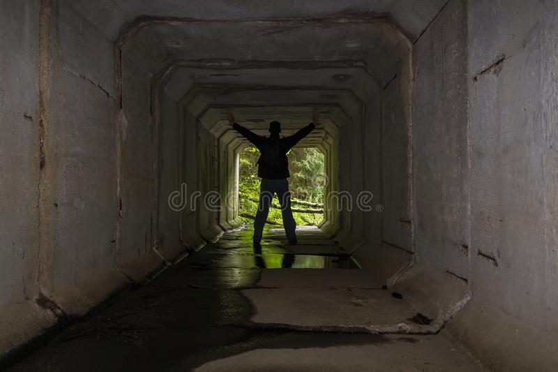 Young man standing on concrete stream tunnel in black jacket with hands up stock images