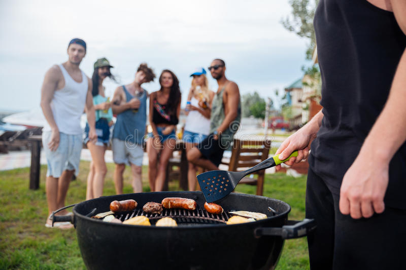 Young man standing and cooking sauseges on barbeque party stock images