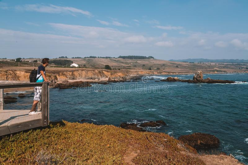 Young man standing on the edge of the pier by the Californian royalty free stock photos