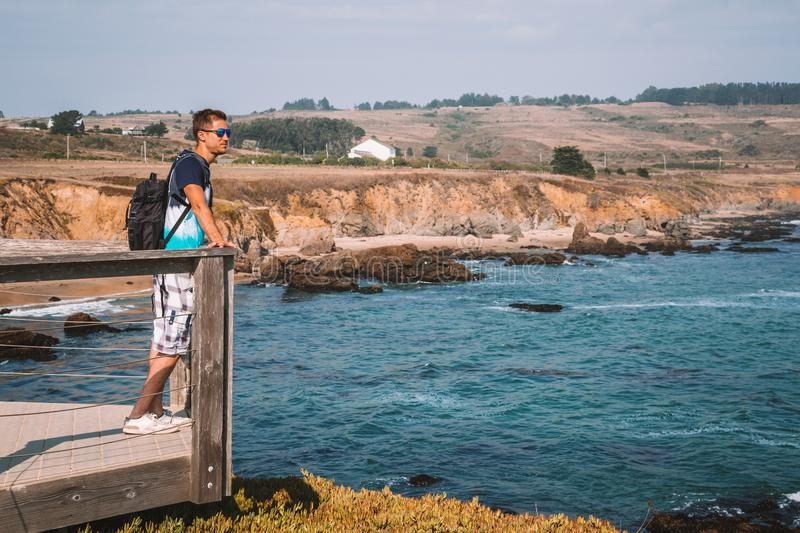 Young man standing on the edge of the pier by the Californian royalty free stock image