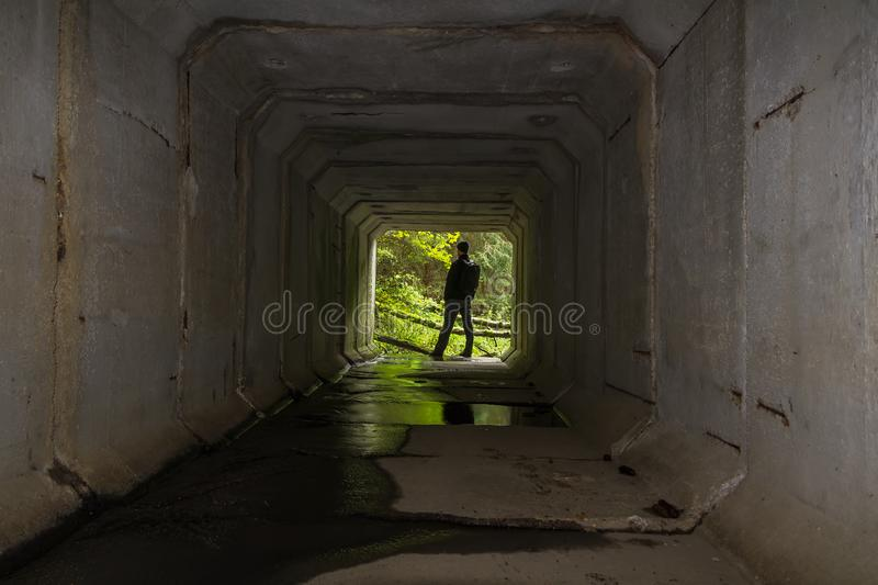 Young man standing on end of concrete stream tunnel in black jacket with backpack royalty free stock photo
