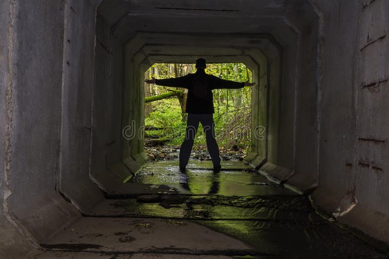 Young man standing on end of concrete stream tunnel in black jacket with backpack and open hand royalty free stock photography