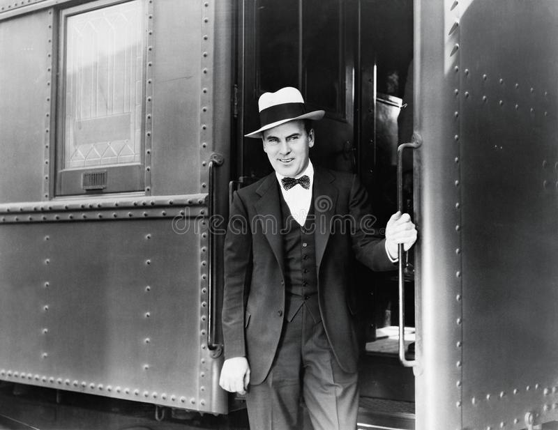 Young man standing at the entrance of a train stock photography