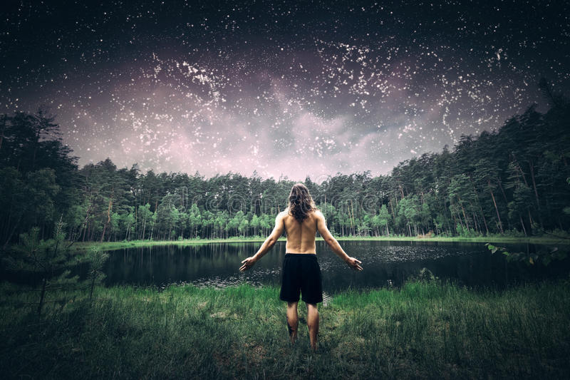 Young man standing in the forest at night. Young man standing in the forest with arms wide open. Inspirational view of a summer night sky full of stars, lake stock photography