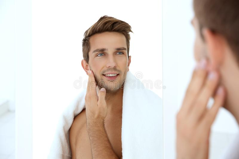 Young man standing in front of mirror. And touching his face royalty free stock image