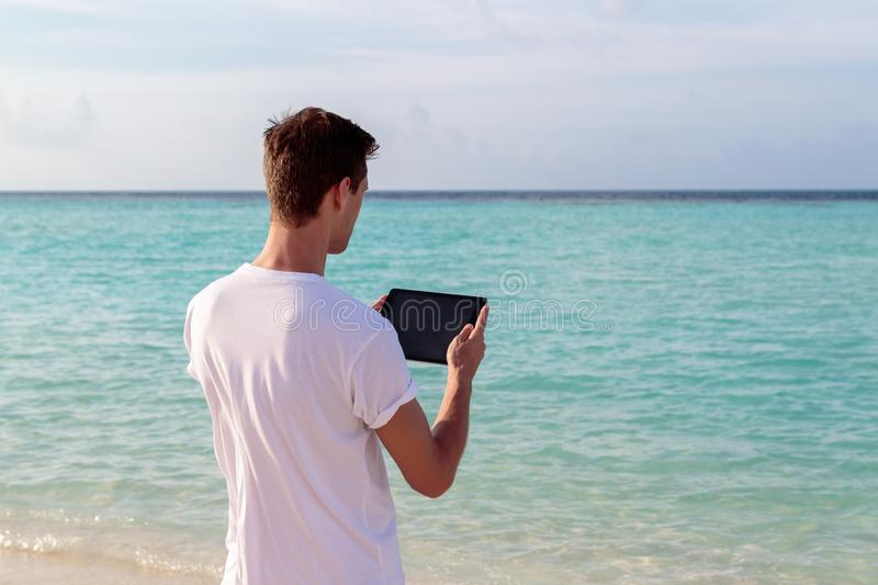 Young man standing in front of the sea and using his tablet during sunset. Boy in holiday in a tropical location using his tablet. clear blue water as background royalty free stock photos