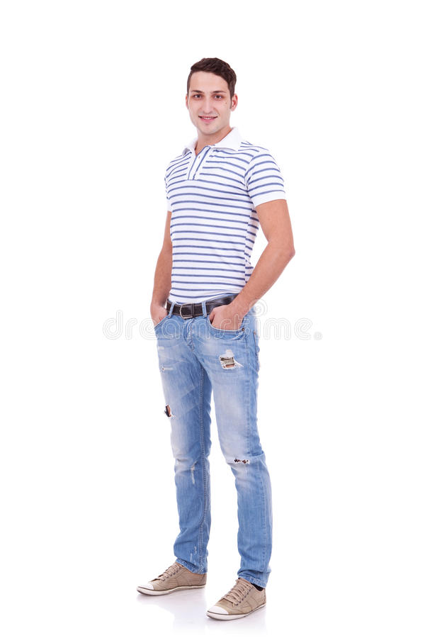 Young man standing with hands in pockets stock photo