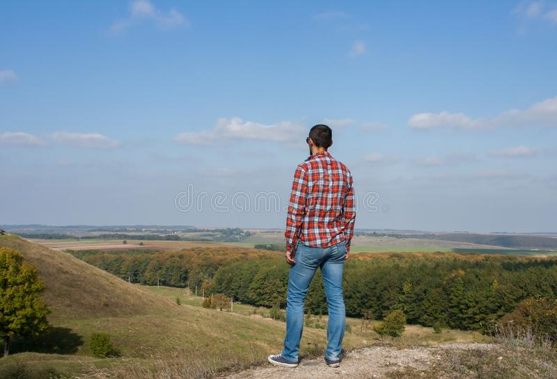 Young man standing on a hill enjoying scenery. Concept of travel and freedom stock image