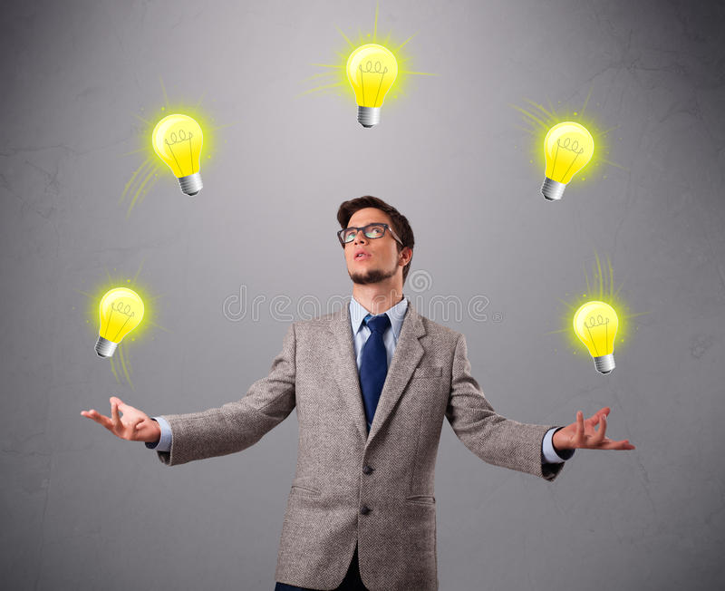 Young man standing and juggling with light bulbs stock image