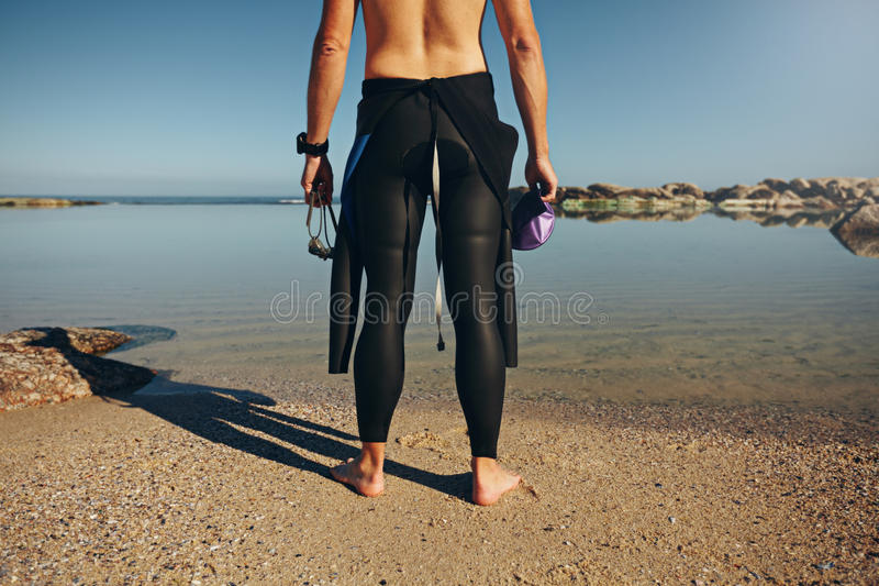 Young man standing on lake wearing wetsuit royalty free stock photography