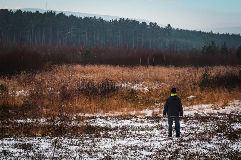 Young man standing landscape with snow and distant hills royalty free stock photo
