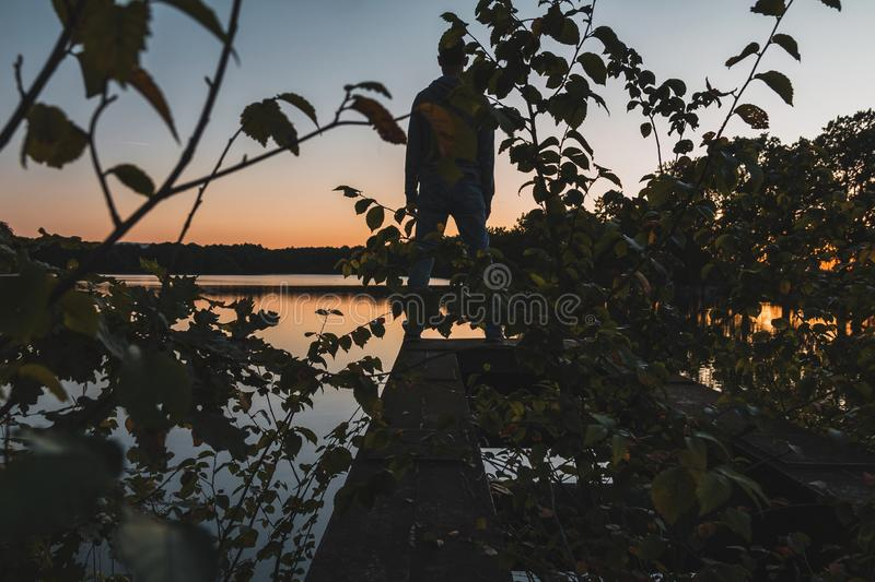Young man standing on metal construction with autumn foliage and pond at sunset. Czech landscape stock photography