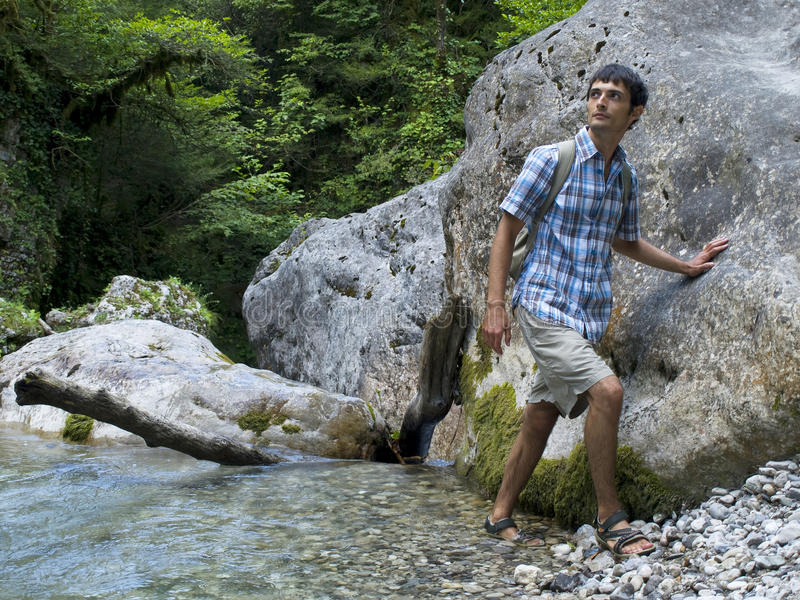 Young man standing near rock in mountain forest stock photo