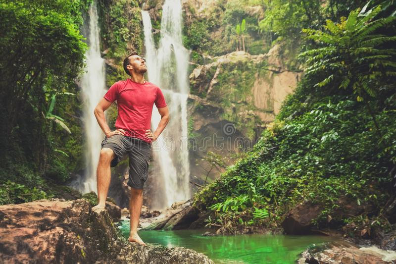 Young man standing near a waterfall in forest. Low angle shot of young man standing near a waterfall in forest and looking away. Male hiker enjoying in the royalty free stock photos