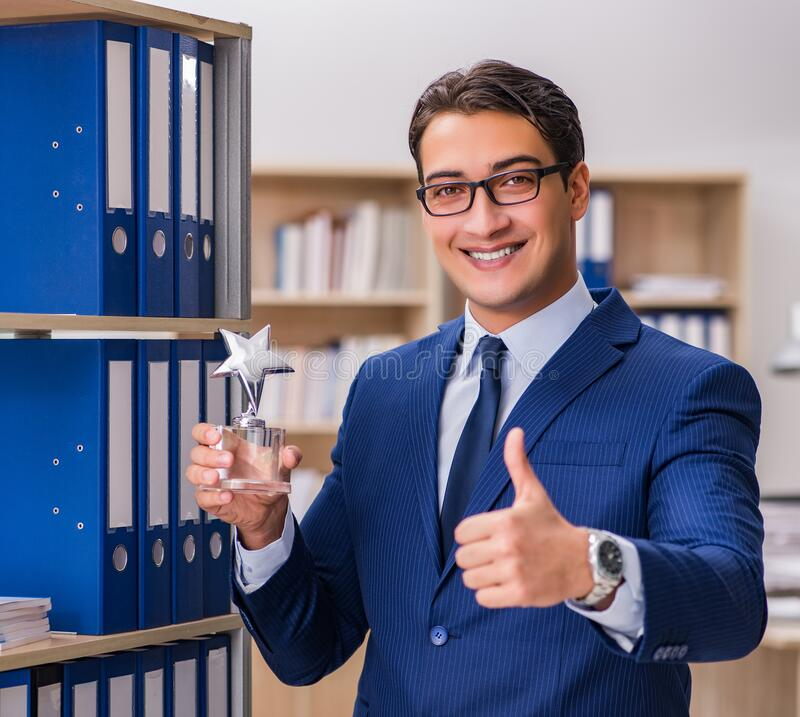 Young man standing next to the shelf with folders stock image