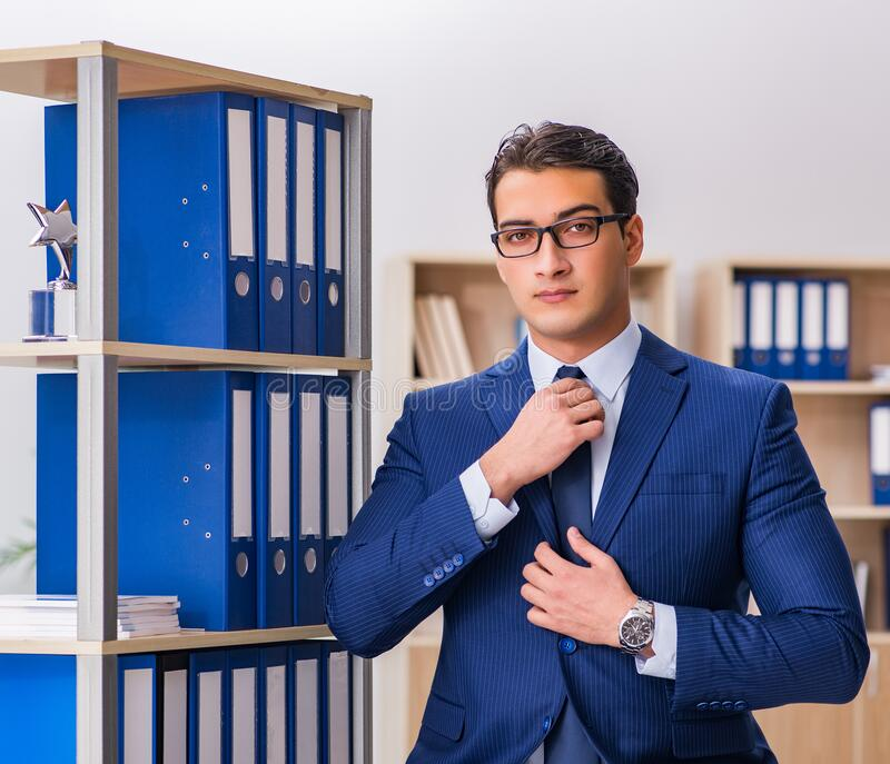 Young man standing next to the shelf with folders stock photo