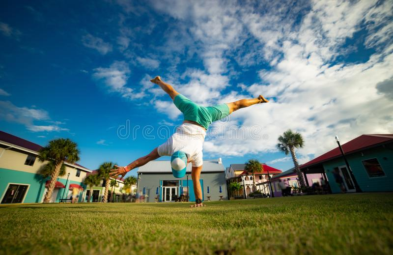 Young man standing on one hand on the grass with blue sky on background royalty free stock photography
