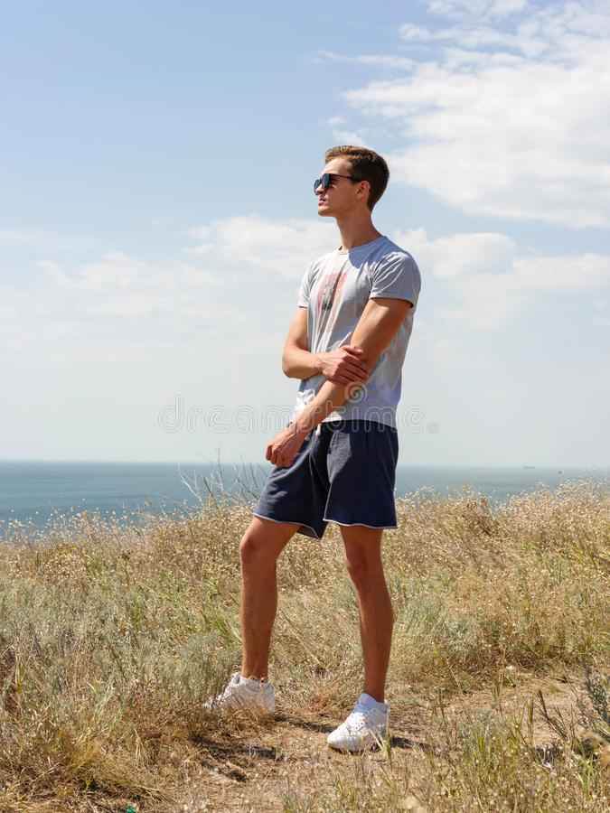 Young man standing and posing on top of cliff in summer mountains at sunset and enjoying view of nature. royalty free stock image