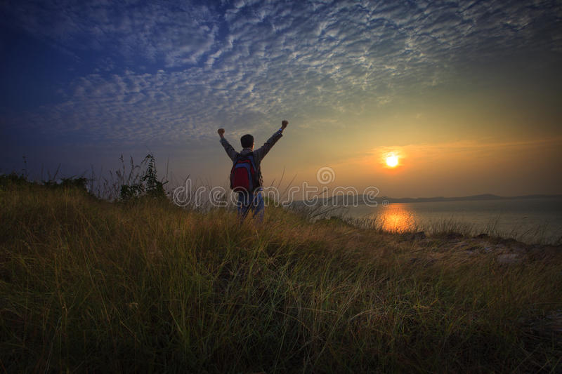 Young man standing and rising hand as victory on grass hill looking to sun above sea horizontal with dramatic colorful sky. File young man standing and rising stock photography