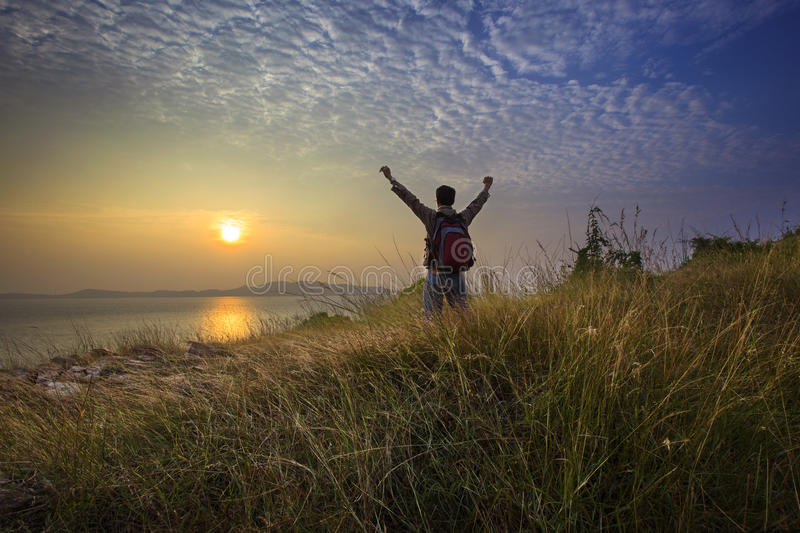 Young man standing and rising hand as victory on grass hill looking to sun above sea horizontal with dramatic colorful sky royalty free stock image