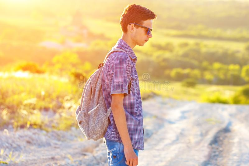 A young man standing on the road with a backpack looking away at the sun stock images