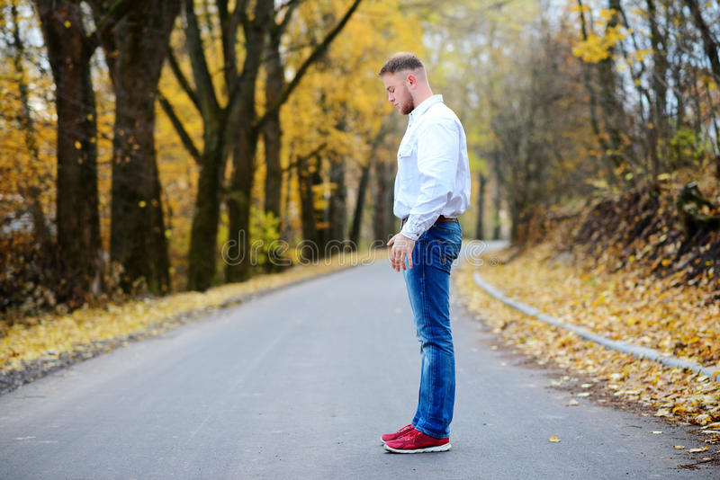 Young man standing on the road in a wonderful autumn day stock photography