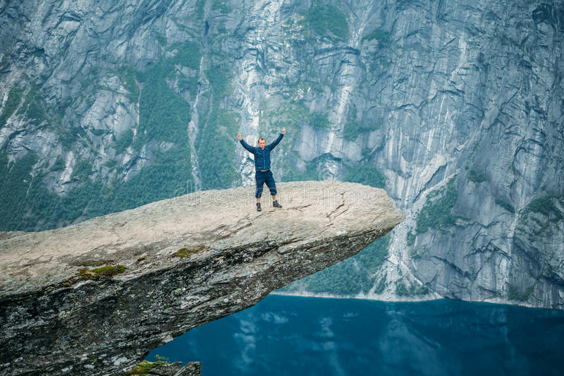 Young Man Standing On Rock In The Mountains Of Norway. Trolltung stock image