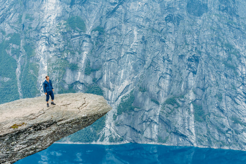 Young Man Standing On Rock In The Mountains Of Norway. Trolltung stock images