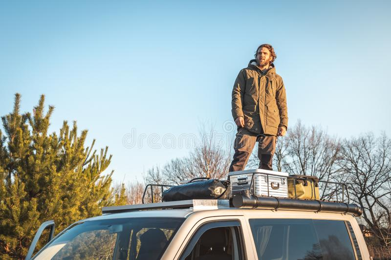 Man on top of his van. Young man standing on the roof rack of a van next to some boxes and gear. The sun is low casting a warm light stock photography
