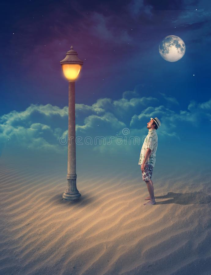 Young man standing on sand looking at an old street lamp. Under clear moon into the night stock photo