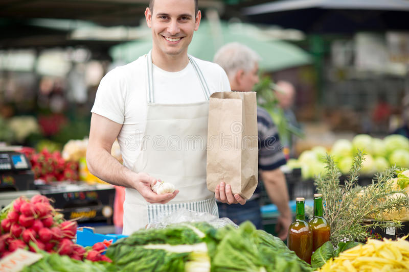 Young man standing on stall fresh food stock photography