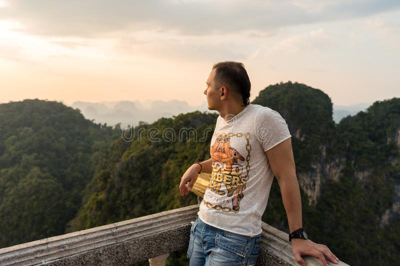 Young man standing in Tiger Cave Temple view point and looks from the high point on. Krabi Province, Thailand - January 16, 2019: Young man standing in Tiger royalty free stock photo