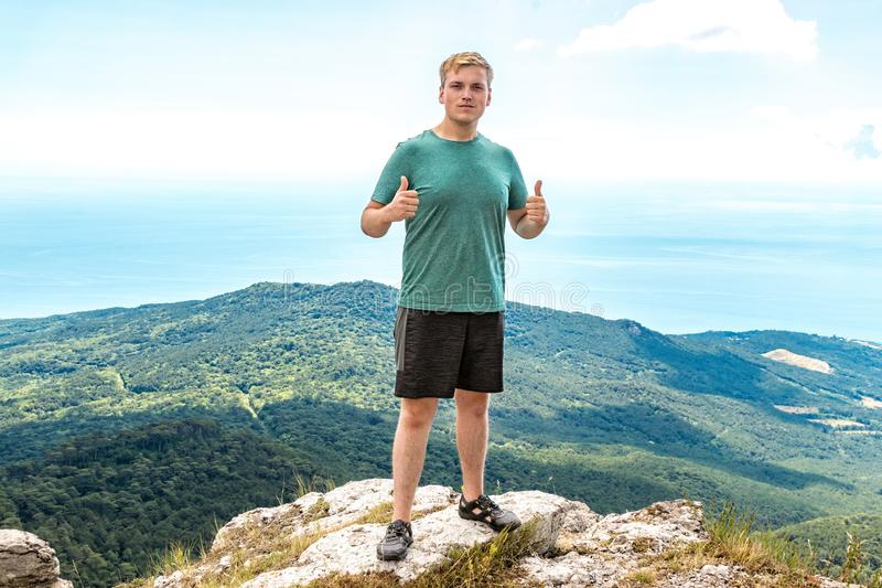 Young man standing on top of cliff in mountains and enjoying view of nature. Mountains and sea stock image