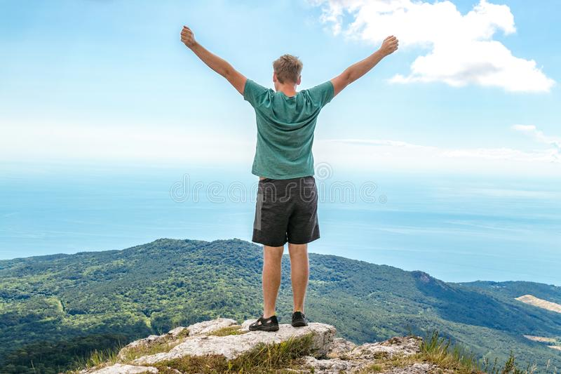 Young man standing on top of cliff in mountains and enjoying view of nature. Mountains and sea stock photography