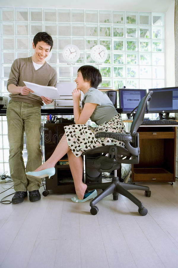 Young man standing by young woman sitting by desk in office, looking at paperwork, smiling stock photos