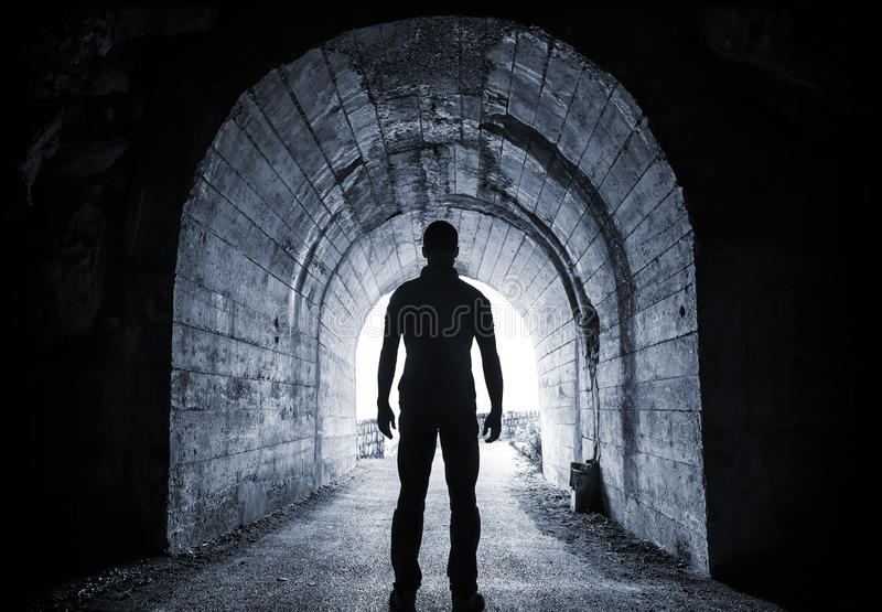 Young man stands in dark tunnel stock photos