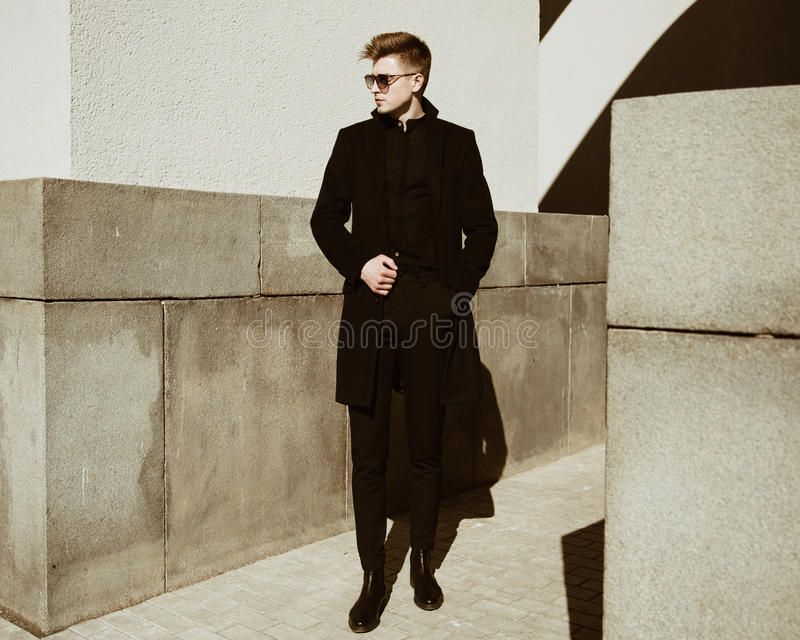 A young man stands near a building stock image