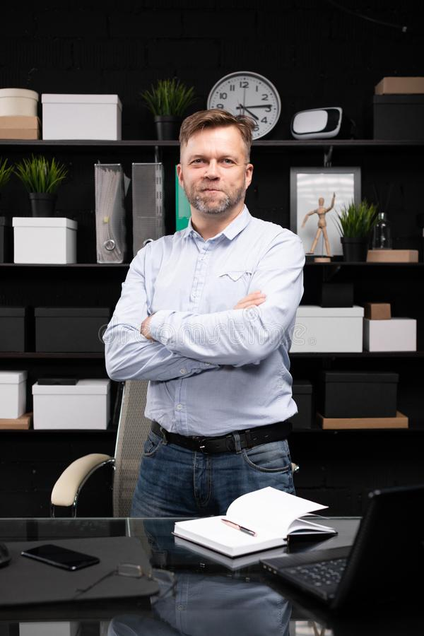 Young man stands near the computer table and folded his hands on his chest. Respectable man stands near computer Desk in stylish office and crossed his arms on stock photos