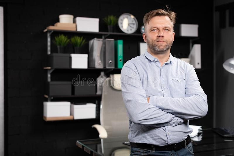 Young man stands near the computer table and folded his hands on his chest. Respectable man stands near computer Desk in stylish office and crossed his arms on royalty free stock photos