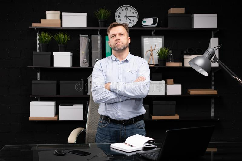 Young man stands near the computer table and folded his hands on his chest. Respectable man stands near computer Desk in stylish office and crossed his arms on royalty free stock photography